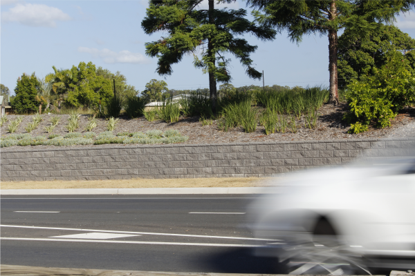 Long_charcoal_road_side_retaining_wall_with_shrubbery_garden_landscapes