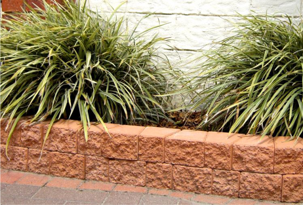 Terracotta_weed_free_garden_edging_blocks_with_grass_plant