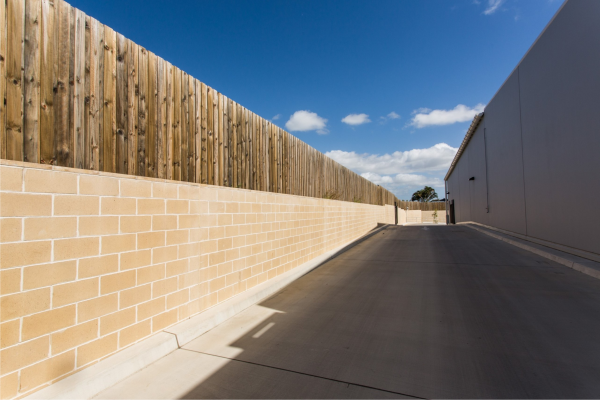 Smooth_cream_coloured_block_retaining_wall_with_white_mortar_topped_with_a_timber_fence_used_beside_the_driveway_of_an_industrial_building