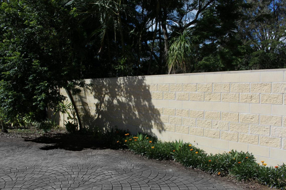 Ivory_coloured_fence_designed_with_split_and_smooth_faced_block_a_small_garden_bed_to_complete_the_finished_project