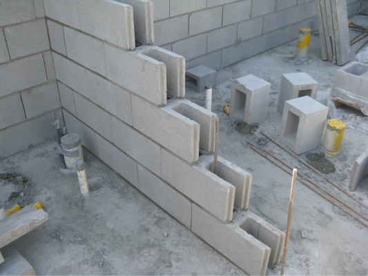 Perp_free_grey_block_wall_half_built_with_starter_bars_and_pipes_showing
