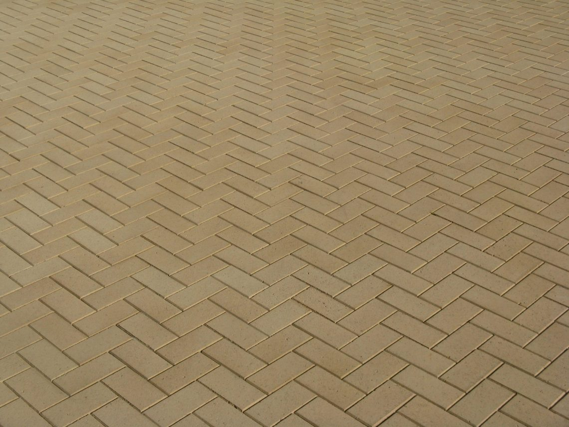 Herringbone_paving_pattern_in_large_outdoor_area_using_small_format_paver_in_Sandstone