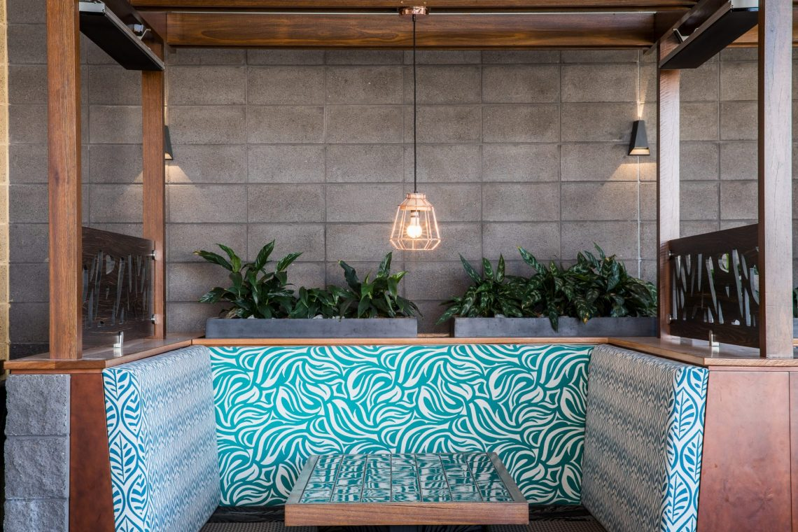 Modern_architectural_restaurant_featuring_smooth_charcoal_coloured_blockwork_with_timber_highlights_and_punches_of_colour_in_the_table_seating_and_surrounding_greenery