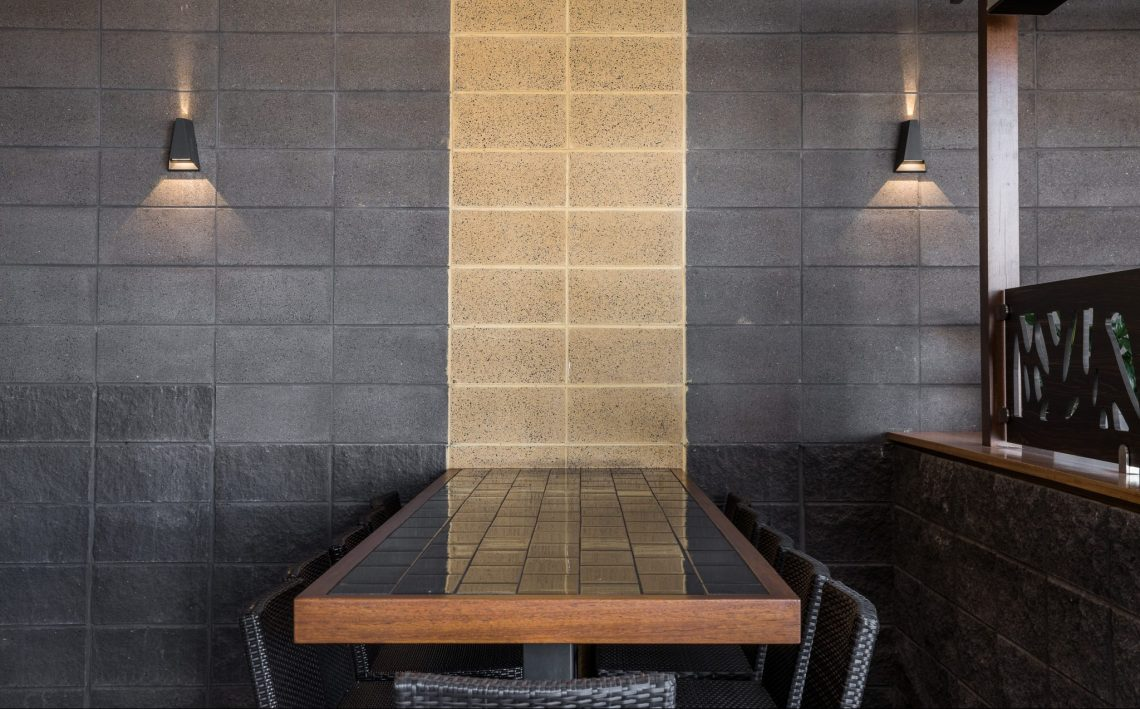 Table_setting_at_a_restaurant_with_a_polished_sandstone_feature_strip_wall_and_smooth_and_splitface_Charcoal_blockwork_with_lights