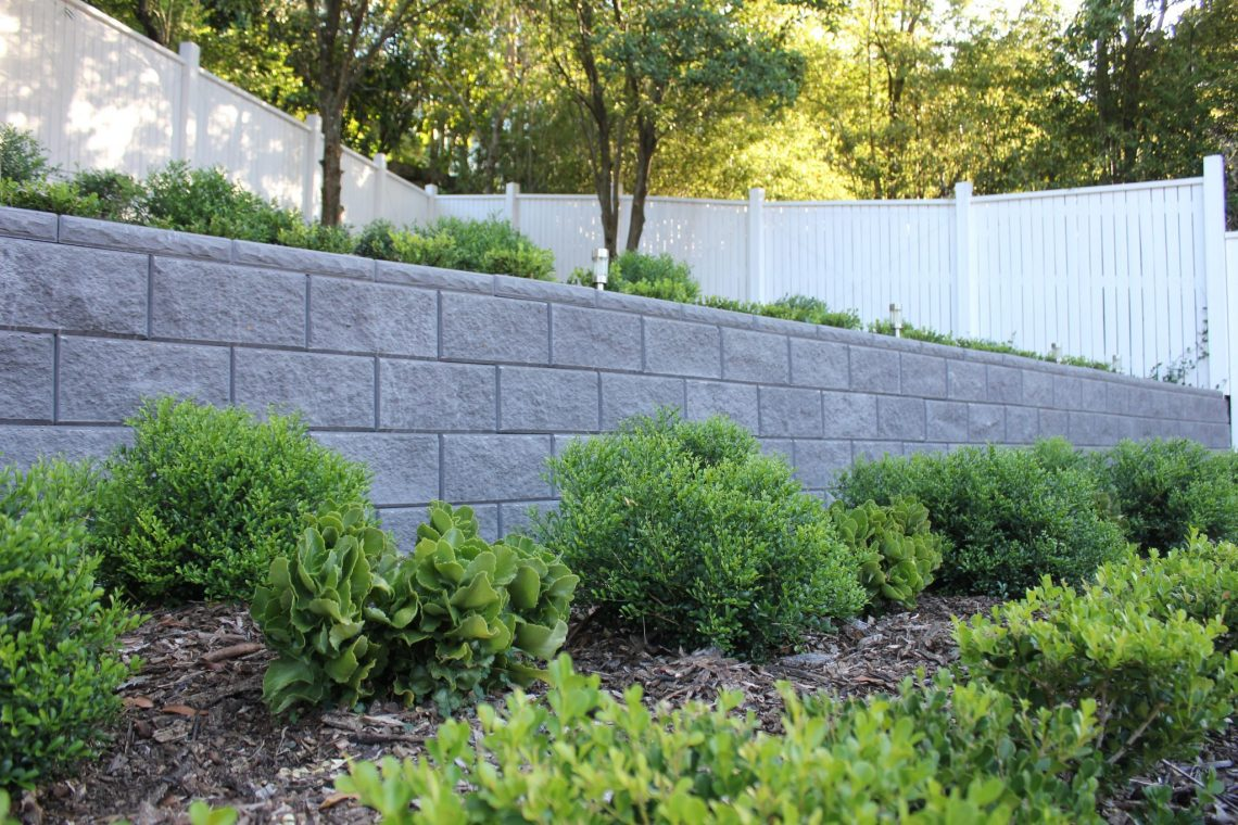 Vertical_drystack_retaining_wall_Charcoal_with_green_shrubbery_and_lights_in_terraced_Garden_Bed