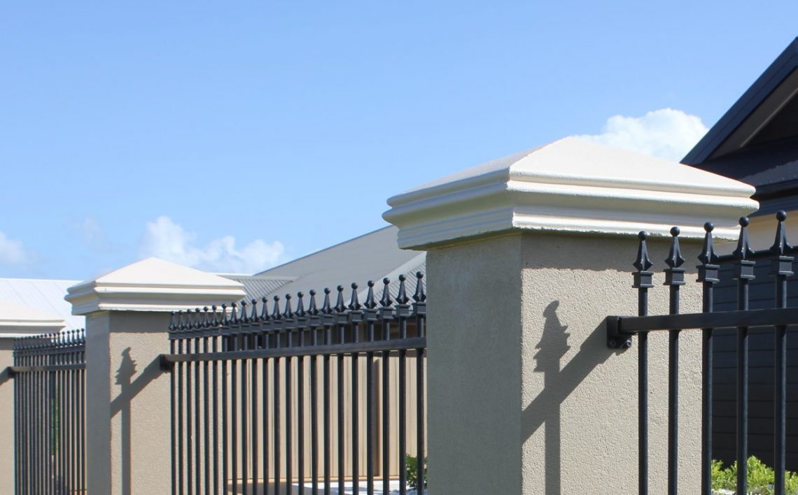 Fenced_property_with_concrete_piers_topped_with_painted_concrete_pier_caps