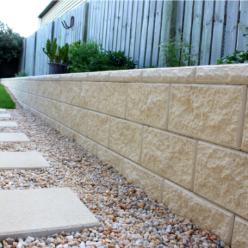 3_blocks_high_Ivory_vertical_faced_retaining_wall_with_a_pebbled_footpath_with_large_format_Ivory_pavers_used_as_stepping_stones