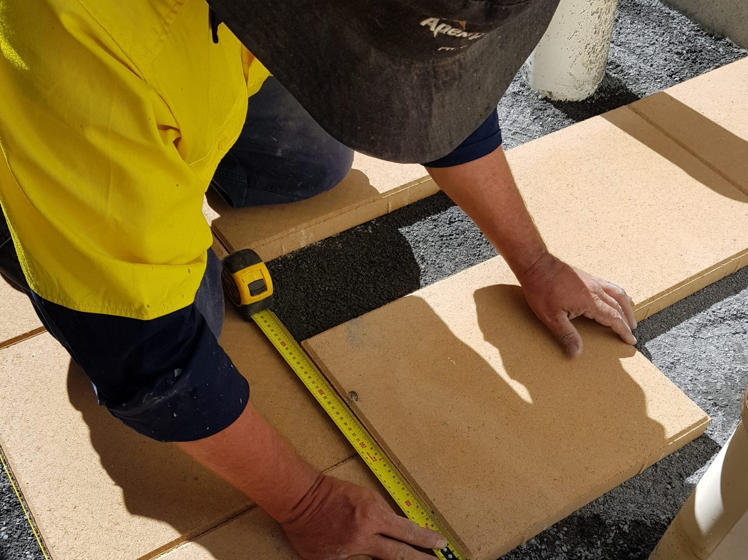 Paving_installer_measuring_pavers_on_crusher_dust.