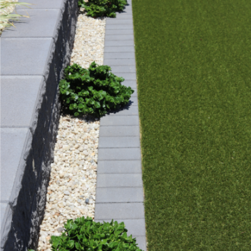 Retaining_wall_supporting_a_pebbled_garden_bed_and_small_format_paver_used_as_a_garden_edge_border_at_a_project_in_Bargara