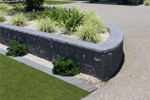 Retaining_wall_garden_bed_curving_in_bond_with_a_row_of_small_format_pavers_creating_a_mowers_strip_at_a_residence_in_Bargara