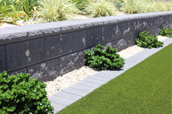 Project_at_Bargara_a_Charcoal_drystack_retaining_wall_behind_a_pebbled_garden_with_small_format_paving_used_as_a_garden_edging