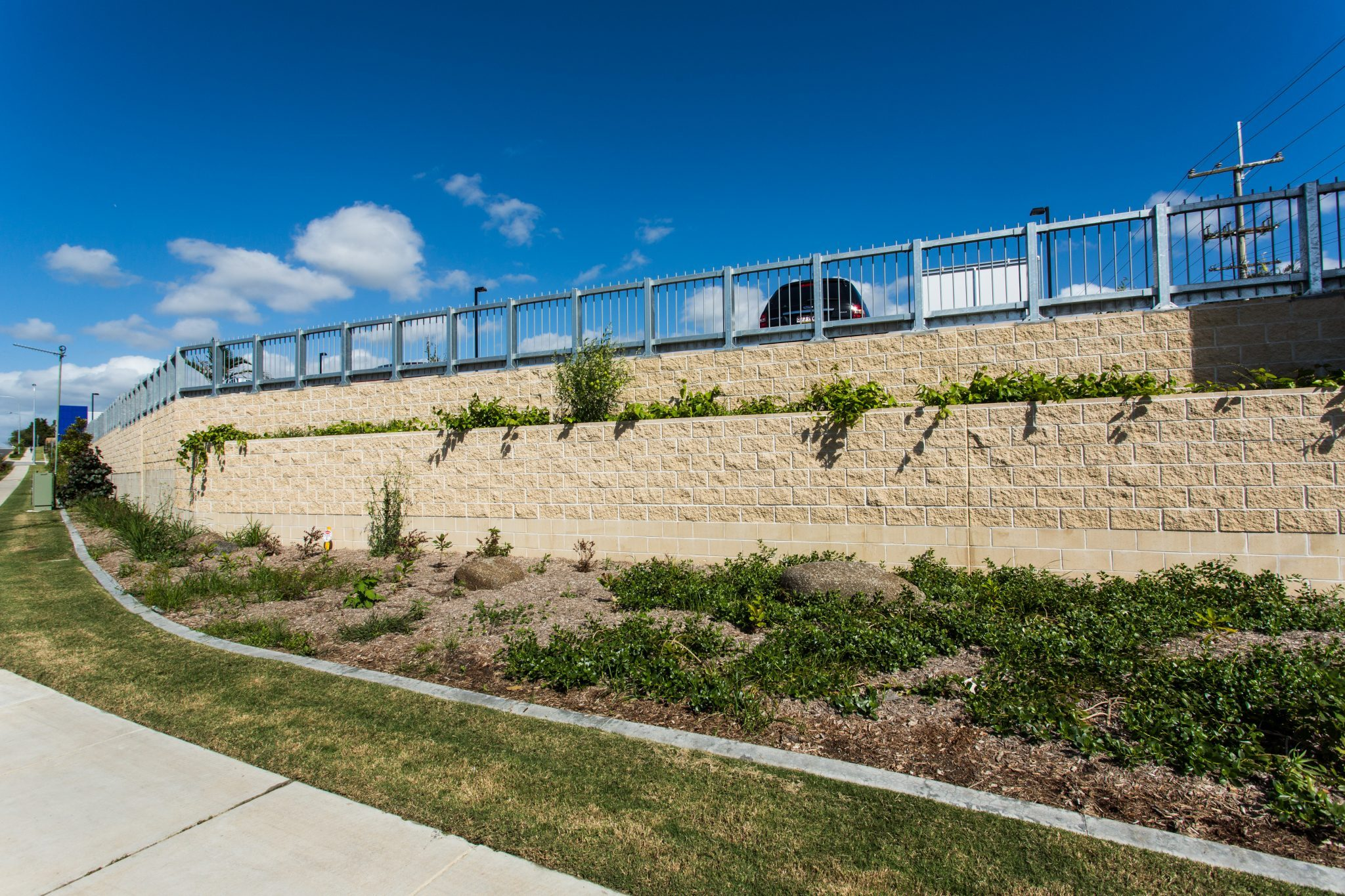 High_Block_Retaining_Wall_featuring a_terraced_Garden_Bed_Supporting_a_Steel_Fence_Barrier_on_top