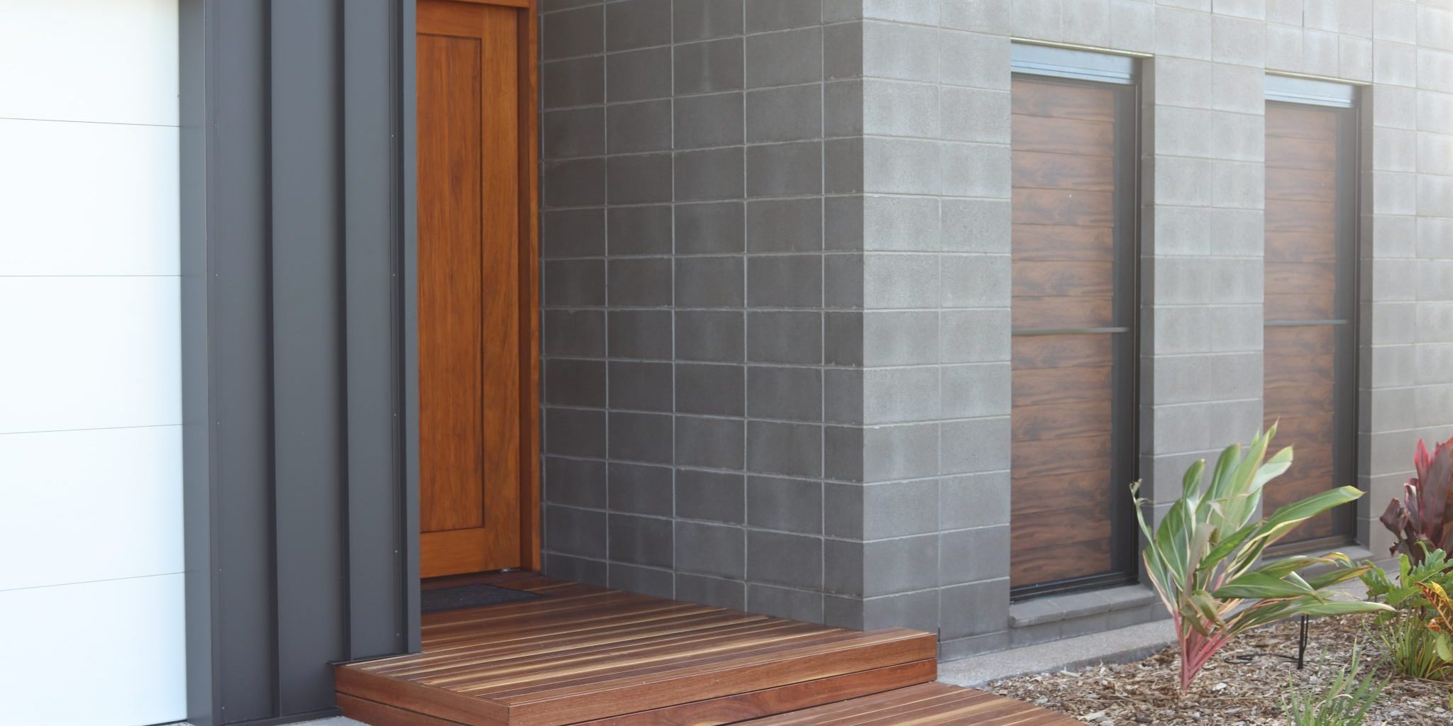 Smooth_Charcoal_Masonry_completing_a_feature_entrance_wall_at_the_front_of_a_home_that_highlights_the_deep_timber_front_door_and_wooden_step